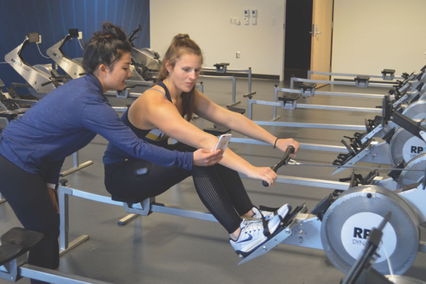 A movement science student shows a young woman on a rowing machine her smart phone