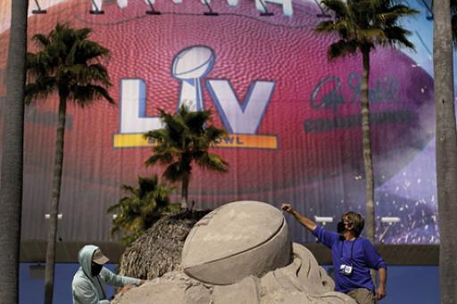 Two people building the Lombardi Trophy out of sand