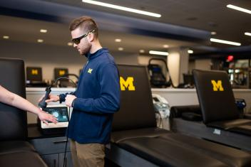 An Athletic Training student uses equipment in the Michigan Football training room